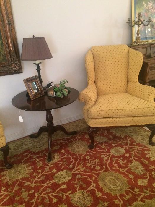 Yellow wing back chair (has matching ottoman); round 3-legged side table