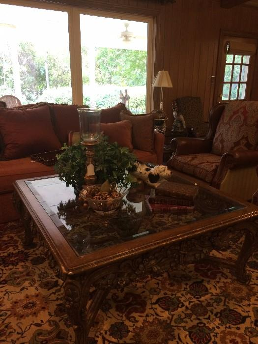 One of two sofas; large ornate coffee table; one of two recliners;