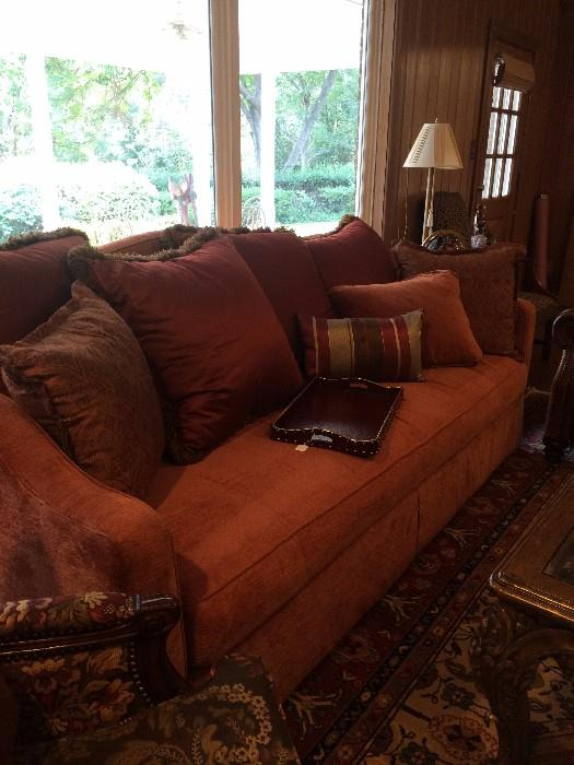 Comfy cinnamon colored sofa with decorative pillows