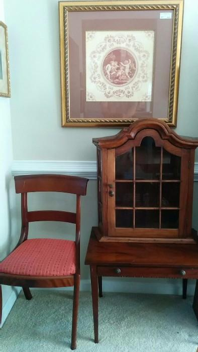 One of the set of 12 sabre-legged mahogany dining chairs, an antique mahogany side table and a mahogany repro 3-shelf hanging cabinet.