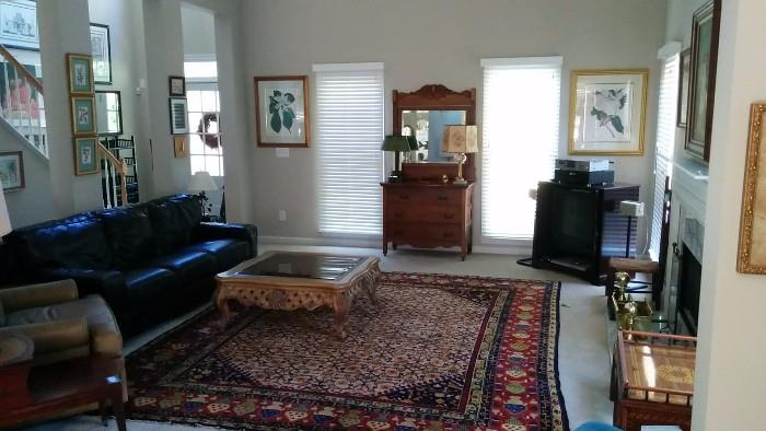 "Overview of the living room. Nice Persian rug, measures 9' 6"" x 11' 6"", smoked & beveled glass-topped wooden coffee table, leather couch, oak dresser/mirror, petite mahogany TV/bar, framed/matted magnolia art."