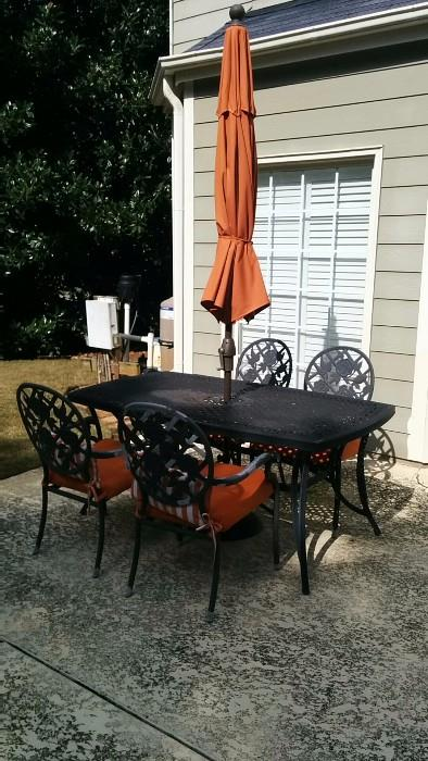 Somber looking wrought iron table and chairs, but you should see it when the umbrella is at full attention!              O M G !