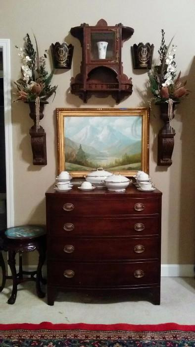 Very somber, yet fetching arrangement of 1940's mahogany 4-drawer (I can count) chest, Asian stool sample with cloisonné top, original artist signed oil on canvas, pair of faux wood (plaster) sconces, cast iron pots with really tacky 1980's Dynasty-ish (Deliverance?) floral stuff spewing out of them, anchored with a very nice Eastlake mahogany hanging cabinet, pair of toile wall vases and, that's finally about it in this pic.