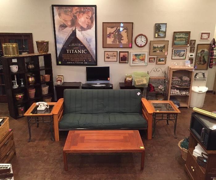 Wall full of art, teak coffee table, futon, glass and cherry end tables, flat screen TV and stand, planters.
