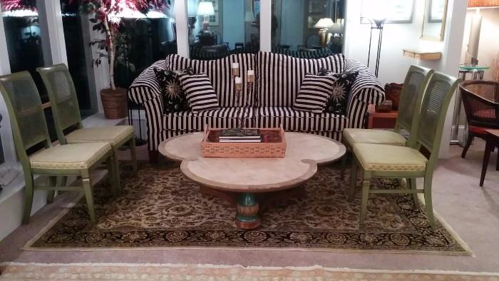Custom made mahogany framed couch, with black/white striped fabric, travertine-topped coffee table, hand-woven, 100% wool rug, 4 of 6 French green side chairs, w/upholstered seats, cane backs.