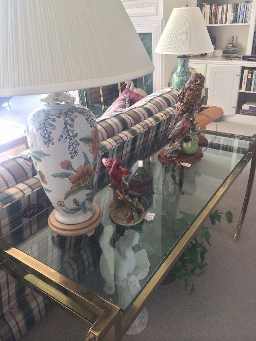 Plaid sofa; brass & glass sofa table; lamps; bird figurines.