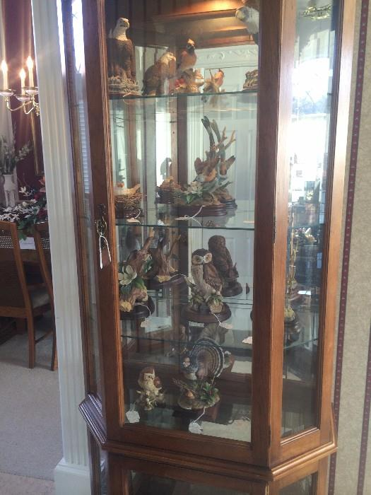 Curio cabinet with bird figurines