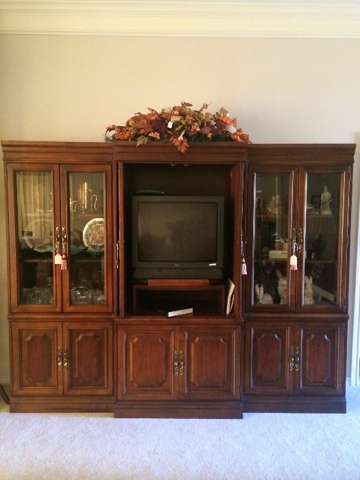 Three unit entertainment center;TV; knick knacks; floral arrangements;