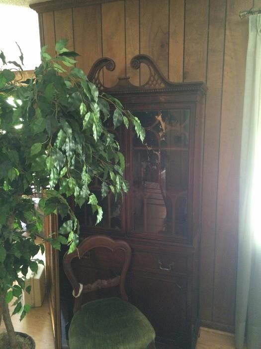 Vintage china cabinet, antique chair and faux plant