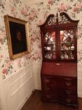 Lighted china cabinet, by Jasper Cabinet, Co, Jasper, IN.                                                                                           The poor soul depicted in the Rembrandt style portrait, was great Aunt Hulga, who was a charwoman and mainly lived in the basement, hence her charming personality so gleefully depicted in oil.