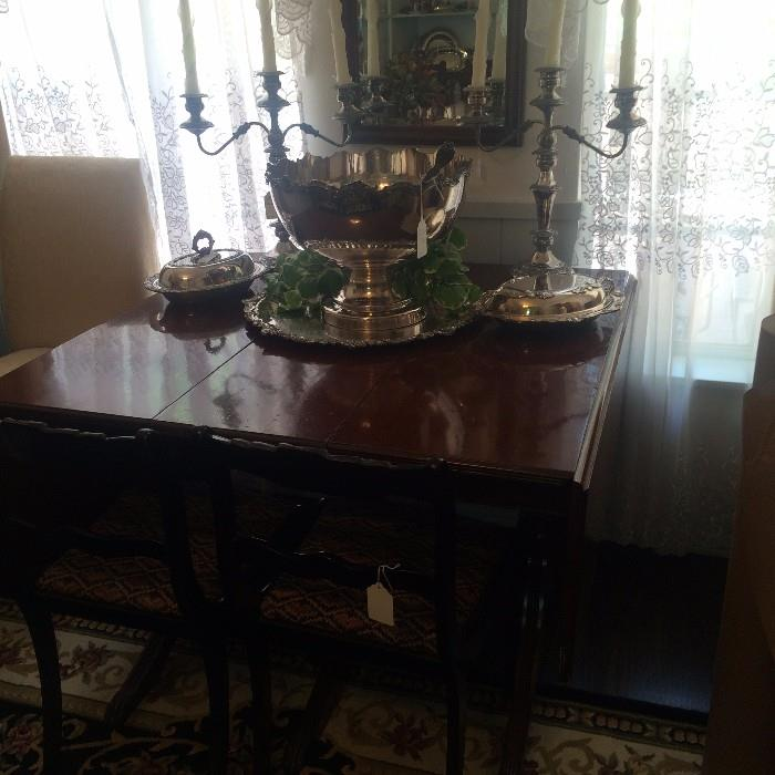 Duncan Phyfe drop leaf dining table; matching silver plate punch bowl and candelabras; beveled mirror