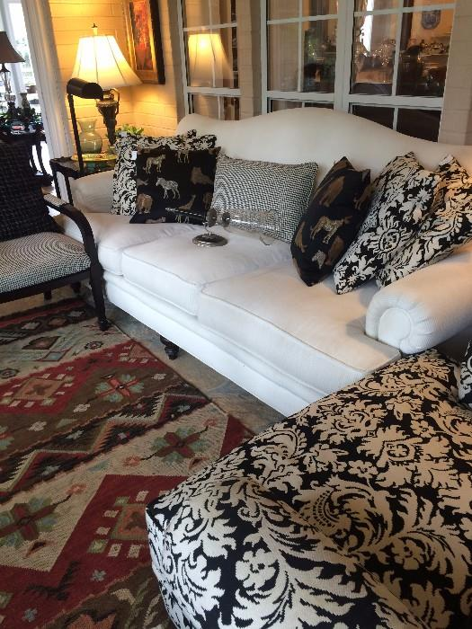 White 3 cushioned sofa; some of the many pillows