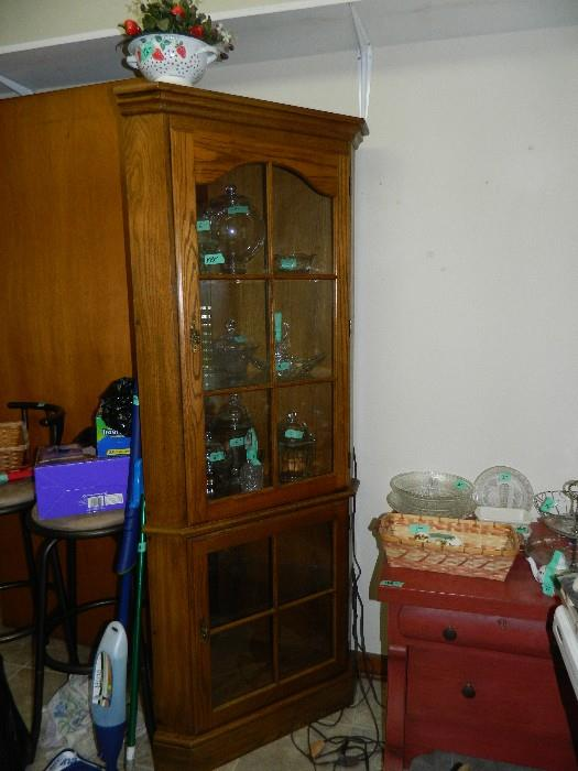 Small curio cabinet filled with glassware & small portable vacuum