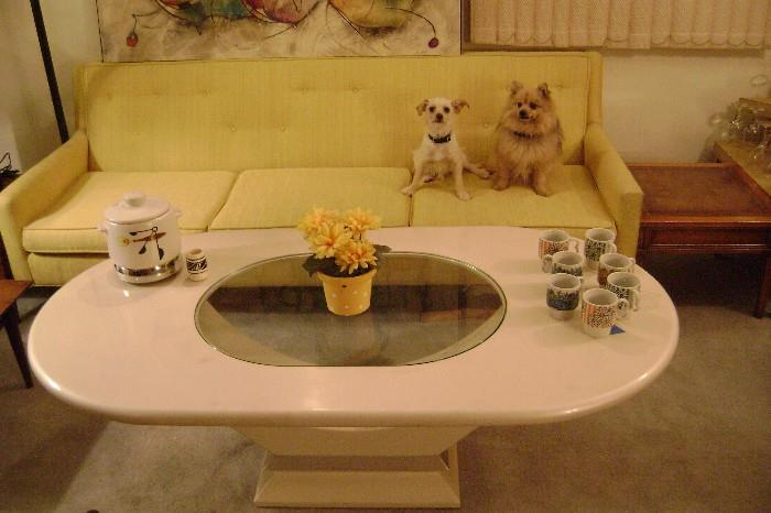 NICE & HEAVY 1980'S MODERN WHITE TABLE AND A YELLOW 1970'S COUCH---OVAL , SEE-THROUGH GLASS TOP---NO STAINS ON COFFEE TABLE---NO BIG STAINS ON COUCH EITHER