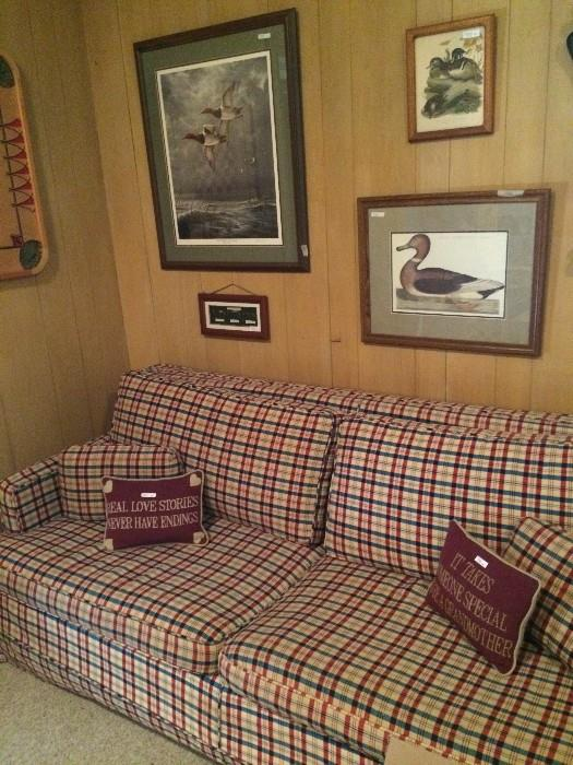 Framed duck prints; plaid sofa