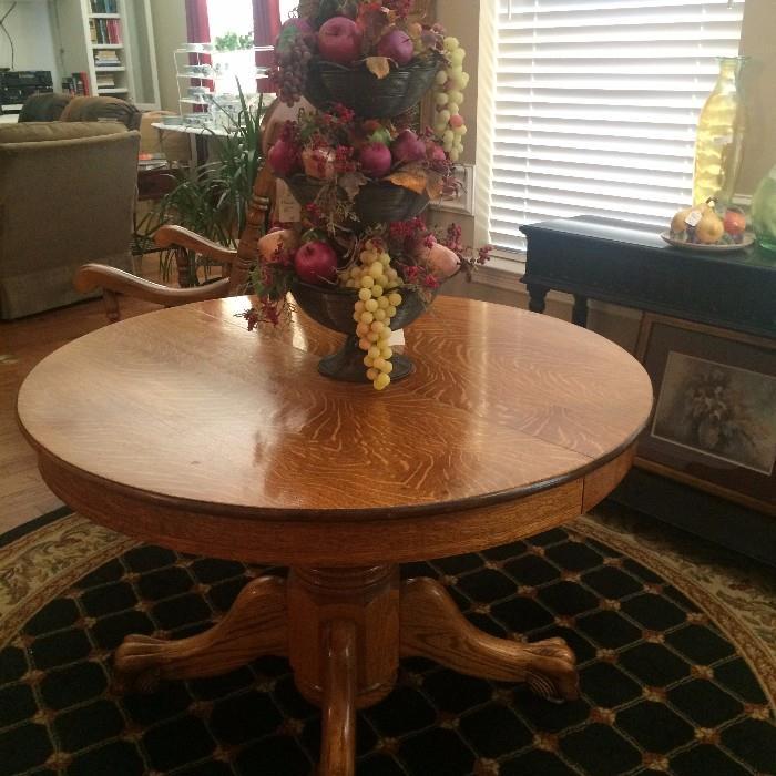 Antique oak table; tierred fruit arrangement; round rug