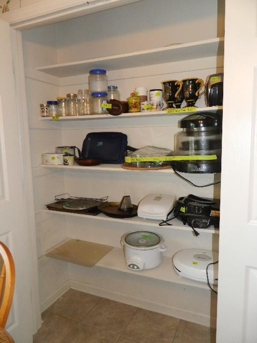 Kitchen pantry:  jars of various sizes, crock pot, grill, miscellaneous other items.