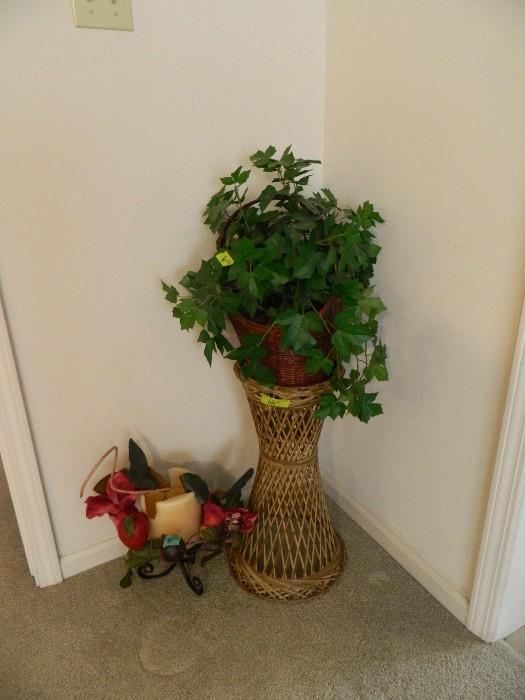Bamboo pedestal with flower arrangement; candle on stand with decor