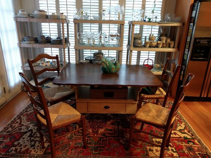 "Quaint wooden breakfast table, with set of four side chairs, jauntily perched atop a wonderful hand-woven Persian Heriz, 100% wool; measures 8' 6"" x 5'.                Trying in vain, is a turquoise chicken on top of the table, straining to lay an egg. She's just not up to it today."