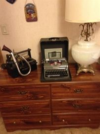 Dresser with vintage lamp, a Dictaphone machine and an Underwood typewriter.