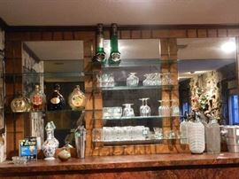Built in bar area in basement with glassware, liquor bottles, seltzer bottles etc