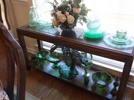 Green depression glass on console table