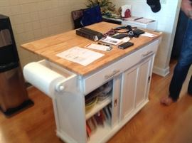 Kitchen island on casters with drop down leaf and a paper towel holder on each end.