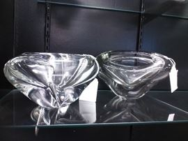 "These modern crystal bowls will electrify any shelf or table they adorn. Each captures the light nearby and reflects it as you can see from this photo. Smooth and artistic, they range in size from approximately 4-1/2"" to 5-1/2"" H x 6"" W x 9 to 10-1/2"" L. The bowl on the right is divided, while the other is not."