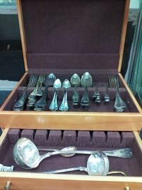 We estimate this continental silver plate service as dating back to the 19th century. The case of 70 pieces includes 2 ladles, 1 sugar spoon, 12 large forks, 11 forks, 11 small forks, 11 soup spoons, 10 large serving spoons, and 12 small spoons.