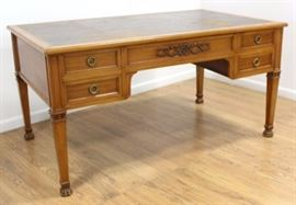 """This early 20th century Louis XVI Style French Satinwood Desk is gold tooled and has a leather top. It has 5 drawers for easy storage. Claw feet and a finished back and sides complete the piece. Oak interior. Approx. 30 1/4"""" H x 58 1/2"""" W x 35 1/2"""" D."""