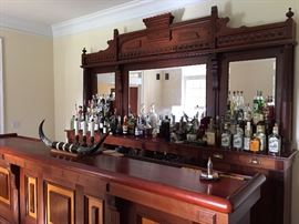 Solid wood bar. The back bar is made from a Philadelphia Walk Through, hand carved detailing. Will be be sold as complete set (front bar, back bar, beer taps, bar stools.  Alcohol belongs to client.
