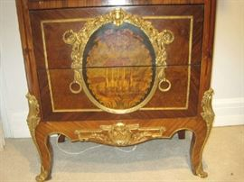 Two drawers in bottom of ornate lighted curio cabinet with painted scene