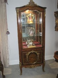 Large  ornate lighted curio cabinet with mirrored back and two glass shelves and beveled glass door and sides