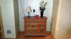 Dresser, lamp, vase with flowers and alarm clock