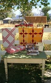 Painted primitive pine table, cotton quilts, and decorating books