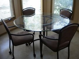 Kitchen table glass top with four armed chairs on casters