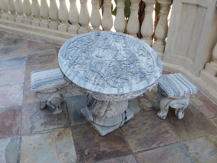 Several sets of carved stone patio furniture