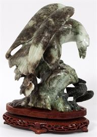 """Lot#16, CARVED SERPENTINE SCULPTURE WITH WOOD STAND, H 9"""" (W/O STAND), EAGLE.Depicts a carved serpentine eagle on a rocky perch mounted on a carved wood footed stand with pierced design."""