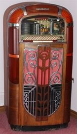 """Lot#22, RMC ROCK-OLA JUKEBOX, C.1945, H 58"""", W 31"""", D 25""""Molded plastic and mahogany case with push buttons along the top, offering a selection of twenty."""