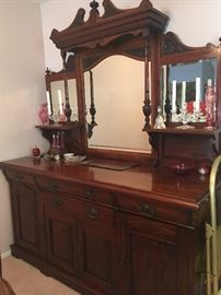 Antique art nouveau buffet with mirror, crystal candle sticks, cranberry glass