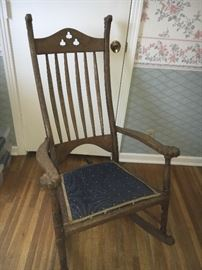 Antique oak rocking chair with shamrock cut-outs on back and carved rosettes on arms.