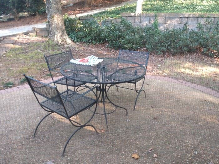 "Lovely wrought iron outdoor dining set. Ol' uncle Billy got drunk one night and rolled down the driveway, never to be seen again.                                                                      IF you're wondering what happened to the fourth chair... AND, what about my ""film noir"" photo talent, shooting this cozy vignette through a screen?!?"