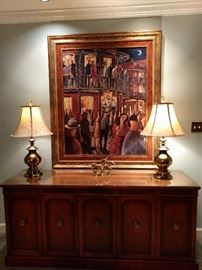 Deluxe Drexel MCM mahogany buffet, with pair of heavy brass lamps, watched over by an original oil, artist signed, of Bourbon Street, New Orleans.