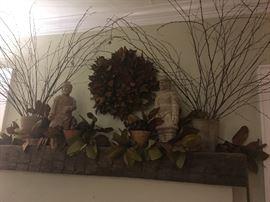 Decorative mantle accessories: faux magnolia, branches, urns, statuary, wreath.
