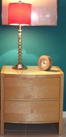 Palliser Furniture Mfg. Canada Mid-Century Style Natural Finish 2-drawer Night Stand with White Glass Top shown with 1 of a pair Chrome Spool Candlestick Lamps and a Silver IKEA Quartz Clock
