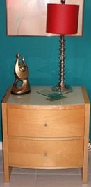 Palliser Furniture Mfg. Canada Mid-Century Style Natural Finish 2-drawer Night Stand with White Glass Top shown with 1 of a pair Chrome Spool Candlestick Lamps, a Silver Plastic Resin Couple with Child Sculpture and a sculptured Glass Pedestal Dresser Tray