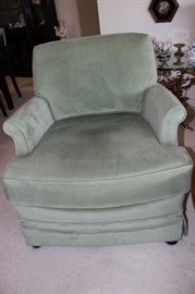 One of two swivel green velvet chairs.