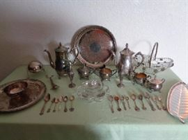 Sterling and Silver plated serving ware  15 serving pieces (not including spoons)  -Misc state spoons, some silver plated most are sterling silver: 15 engraved spoons  -Serving plate: International Silver Co -Salt and Pepper shakers: Trent -Dolphin bottle opener -Candy dish -2 Creamers -2 Pitchers (one being Leonario Silver Plated) -Small vase -Long serving plate -Serving plate with attchated bowl -Glass and metal fruit bowl with leaf and vine design -Butter bowl made in England