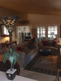 Pair neutral sofas, rug, tables, lighting