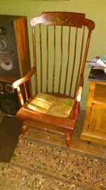 A pair of JBL Stereo Speakers or HiFi speakers. A vintage hardrock maple Rocking Chair. A worn Persian Style Machine made rug. A modern microwave cart on wheels.